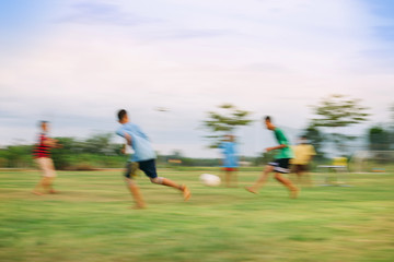 Speed motion blur picture of kids having fun playing soccer football for exercise in community rural area. Concept for sport background with anonymous people.