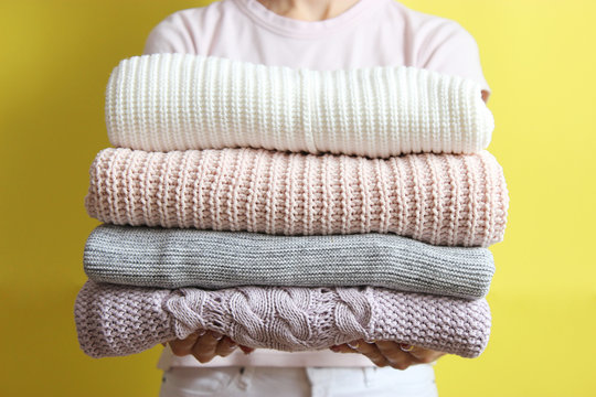 a stack of sweaters in women's hands on a colored background