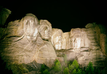 Fotomurales - Mt. Rushmore national memorial park in South Dakota at night, presidents faces illuminated against black sky