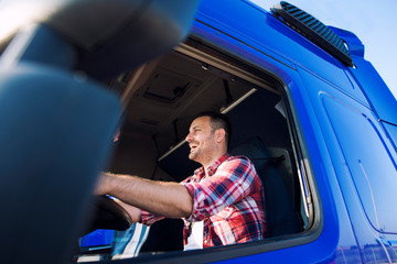Truck driver occupation. Professional middle aged trucker in cabin driving truck and smiling. Transportation industry. Wall mural