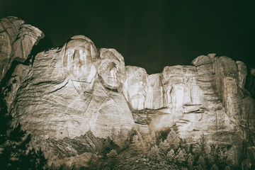 Fototapete - Mt. Rushmore national memorial park in South Dakota at night, presidents faces illuminated against black sky