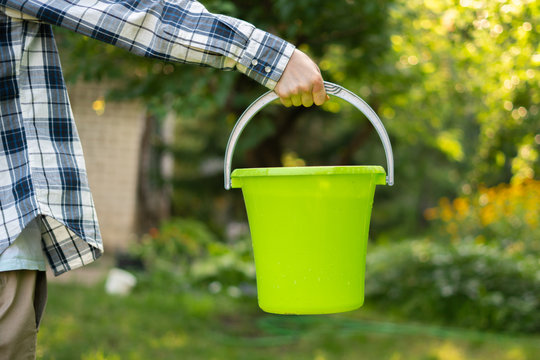 holding a color plastic bucket with pure water