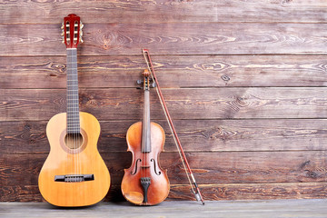 Vintage musical instruments and copy space. Retro guitar and violin on wooden background. Classical musical instruments.