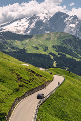 Fototapete - Idyllic Alps with road on green mountain hill