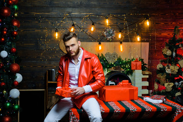 Man well groomed hipster in front of christmas decoration and new year background. Merry christmas and happy new year. Christmas gifts. Man fashionable stylish handsome santa with gift box surprise
