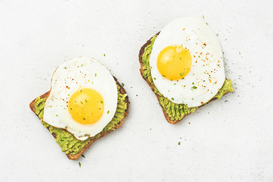 Toast with avocado and egg on concrete background. Table top view