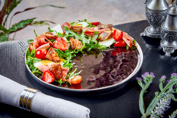 Close up view on Rucola and Fuagra Salad on red plate on dark background. Luxury food concept. Restaurant food bacground. Salad with fuagra, strawberry. clean eating, dieting food concept