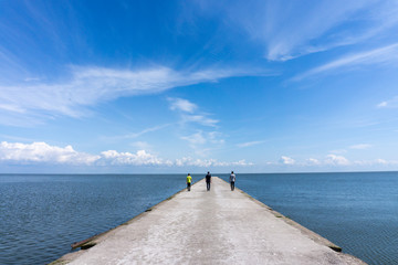 Three people walking along a pier towards the sea
