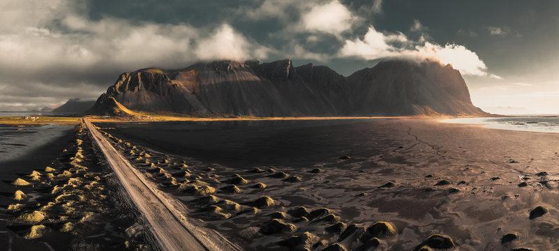 Famous Vestrahorn mountain in Stokksnes, Iceland. Sunrise on beach full of tufts of grass.