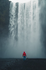 Skogafoss waterfall Iceland. Man standing against huge waterfall surrounded by green hills. Spring in Iceland.