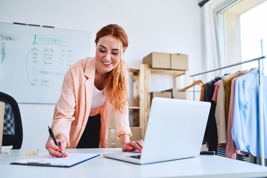 Young woman marking deliveries on clipboard and looking at laptop in office