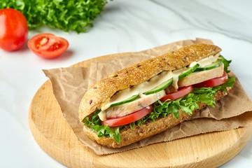 Keuken foto achterwand Snack Big sandwich with chicken and vegetables on wooden board