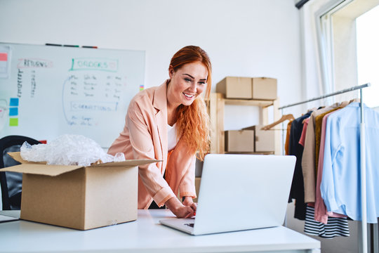 Small business concept. Woman looking at laptop while packing sold items in office