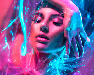 Spoed Fotobehang Beauty Fashion model woman in colorful bright neon lights posing in studio through transparent film. Portrait of beautiful sexy girl in UV. Art design colorful makeup