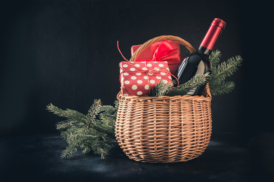 Christmas gift hamper with red wine and gift on black. Space for your greetings. Xmas card.