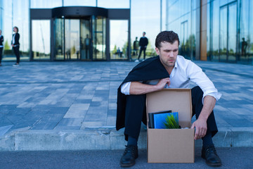 Fired business man sitting on street