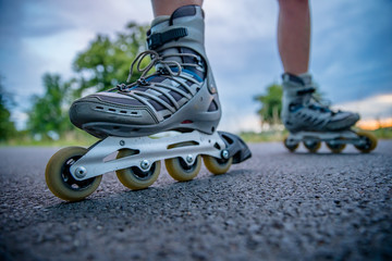 roller skates in action on the asphalt trail at freestyle races outside the city