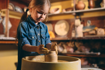 Pottery workshop. A little girl makes a vase of clay. Clay modeling