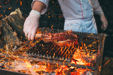 Chef Cooking steak. Cook turns the meat on the fire. Wall mural
