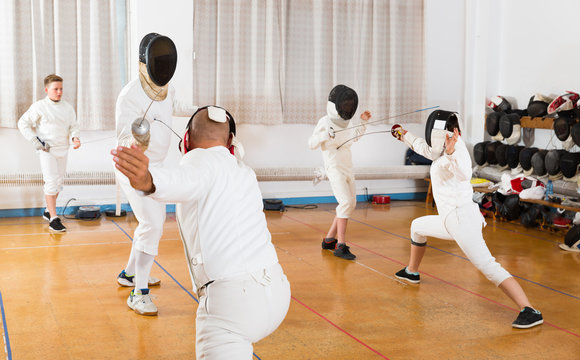 Adults and teens wearing fencing uniform practicing with foil