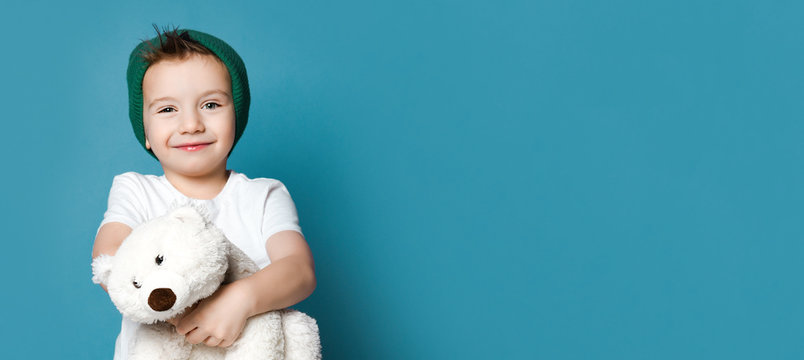 Little boy in green hat hold polar bear toy smiling. International day of polar bear concept