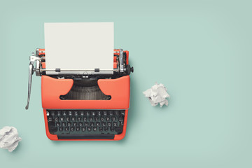 red vintage 60s / 70s typewriter with blank page and paper balls on a bright green desk, retro workspace or office design elements