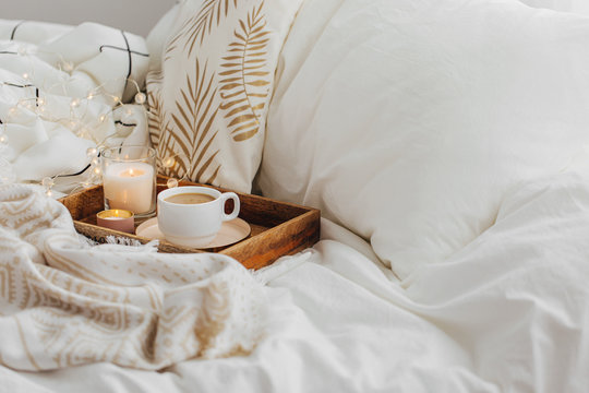 Wooden tray of coffee and candles on bed. White bedding sheets with striped blanket and pillow. Breakfast in bed. Hygge concept.