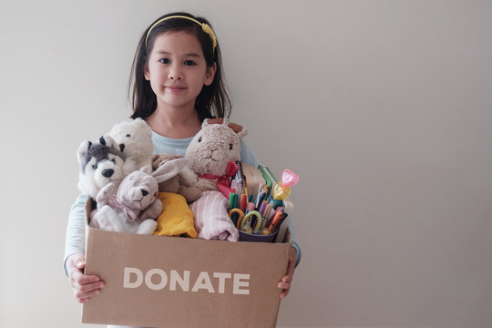 Mixed Asian young volunteer girl holding a box full of used old toys, cloths, books and stationery for donation, act of kindness