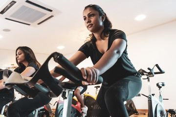 Fit people working out at spinning class in gym