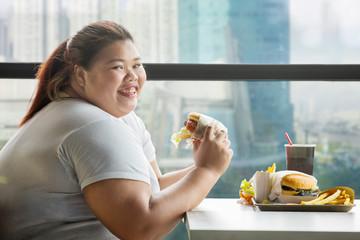Happy fat woman eats a hamburger in restaurant