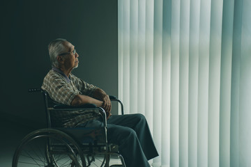 Pensive senior man sits in the wheelchair