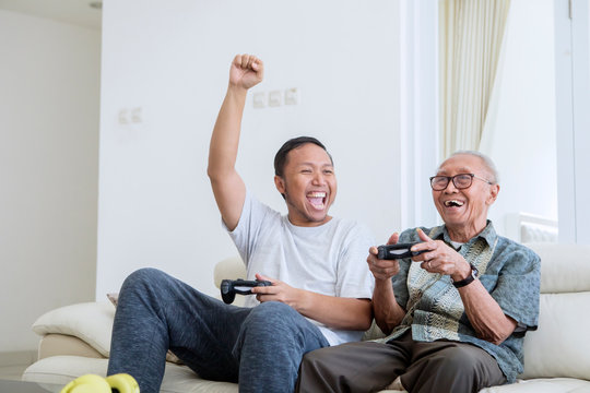 Young man playing video games with his father