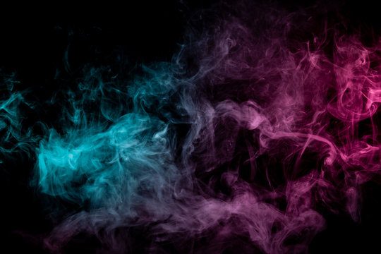 Colored background with winding clouds of smoke from patterns of different forms of pink, green and blue colors with tongues of flame on a black isolated background. Print for t-shirt.