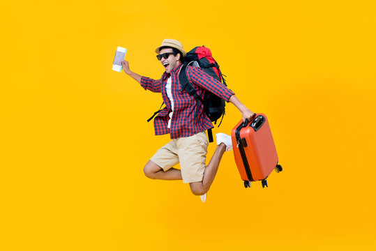 Happy Asian man with air ticket jumping