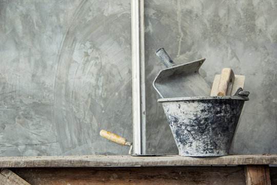 Set Plastering tools concrete to build wall with Gyan plaster, trowel concrete in basket on scaffolding and Background gray surface wall bare cement skim coat loft style for interior or exterior.
