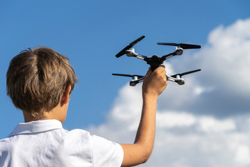 Boy playing with drone in summer day outdoors against blue sky Wall mural