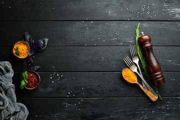 Wall Mural - The background of cooking. On a black wooden background. Top view. Free space for your text.