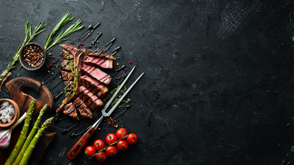 Tuinposter Steakhouse Beef T-Bone steak on a black table. Top view. Free space for text.