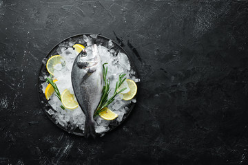 Fototapete - Raw dorado fish with lemon and spices on a black background. Top view. Free space for your text.