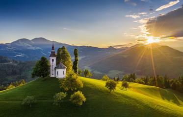 Obraz Skofja Loka, Slovenia - Aerial view of the beautiful hilltop Sveti Tomaz (Saint Thomas) church with a warm summer sunset, clear blue sky and Julian Alps at the background - fototapety do salonu
