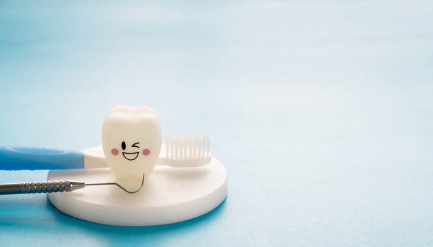 Dental tools and smile teeth model on blue background.