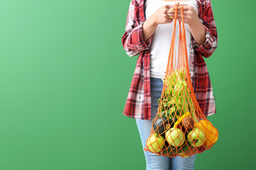 Woman holding mesh eco bag with products on color background