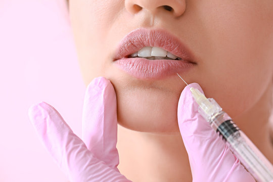 Young woman receiving injection of filler in lips, closeup