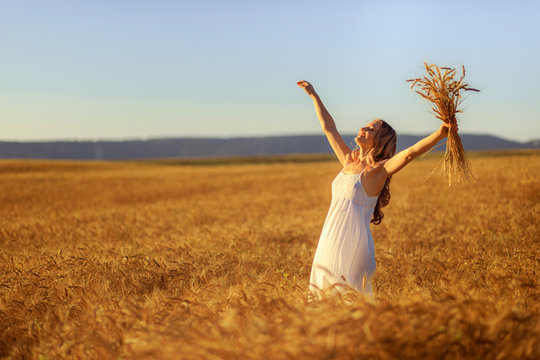 Beautiful young woman in wheat field at sunset outdoor .
