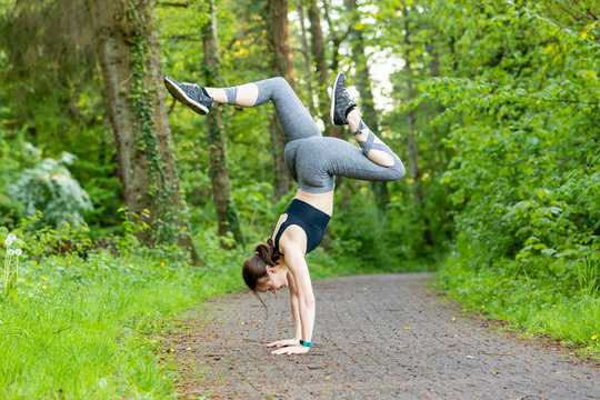 young woman doing a handstand as a fitness workout