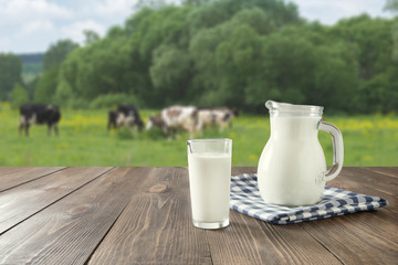 Fresh milk in glass on dark wooden table and blurred landscape with cow on meadow. Healthy eating. Rustic style.