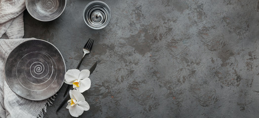 Elegance table setting with knitted grey napkin, cutlery, ceramic plates, glasses and white orchid flowers