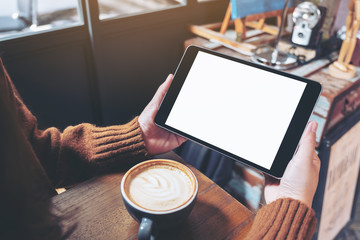 Mockup image of hands holding black tablet pc with blank white screen with coffee cup on wooden table