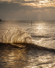 Waves backlit by the dawn sun reflect off the sea wall and impact with an incoming one, Exmouth, Devon