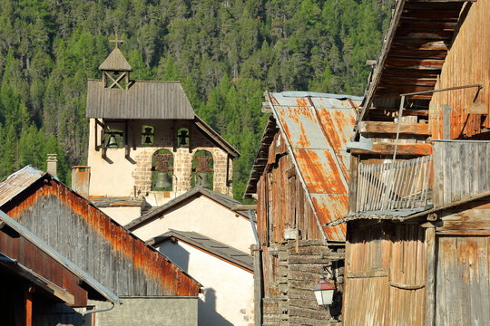 Traditional wooden houses with the bell tower of Saint Sebastien Church in the background, Ceillac, Queyras Natural Park, Southern Alps, France
